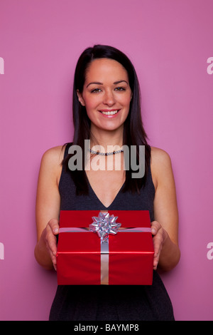 Brunette woman holding a present wrapped in red wrapping paper with silver bow pink background - Stock Photo