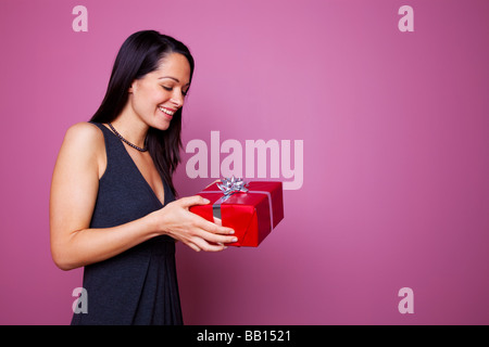 Woman smiling as she receives a present wrapped in red wrapping paper with silver ribbon and gift bow - Stock Photo