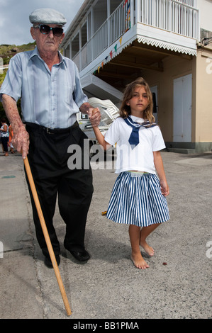Young girl leads elderly man with stick Saint Louis Festival Corossol St Barts - Stock Photo