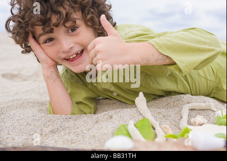 Boy showing thumbs up sign on the beach - Stock Photo