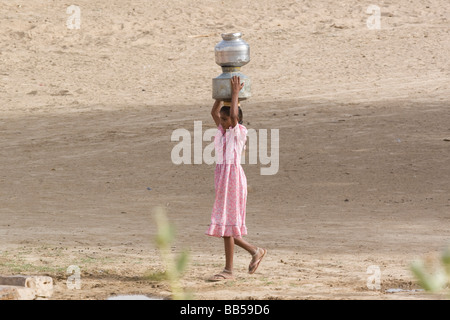 India Rajasthan Masuria young girls carrying water from the well back to the village in a jug on her head - Stock Photo