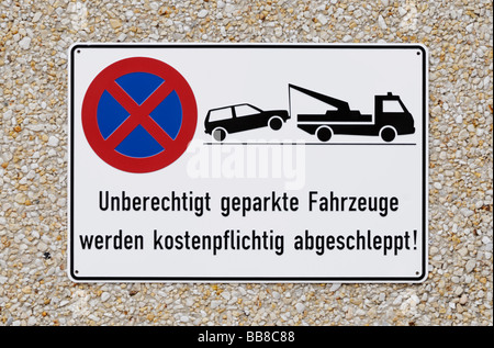 Sign on gravel concrete, unauthorised cars will be towed of, owner will be liable to pay costs - Stock Photo