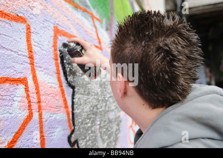 Teenage boy working on a grafitti piece on an exterior wall. - Stock Photo