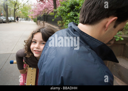 A young girl on a wooden scooter peeking around her father - Stock Photo