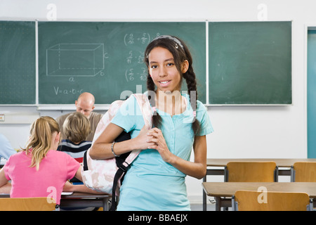 Portrait of a schoolgirl standing in a classroom - Stock Photo