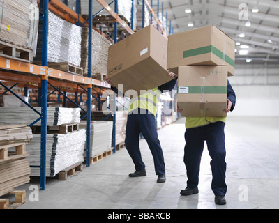 Men Struggling With Boxes In Warehouse - Stock Photo