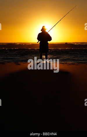 Fisherman on beach at sunrise - Stock Photo