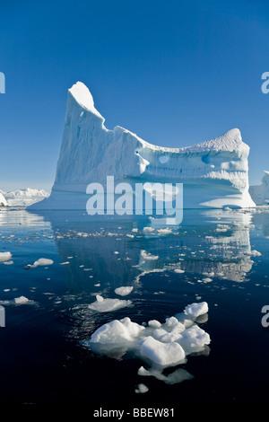 Gigantic Iceberg and its Reflection in Wilhelmina Bay off Enterprise Island in the Antarctic Peninsula - Stock Photo