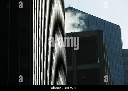 High rise office buildings side by side, steam vapor billowing from rooftop, low angle view - Stock Photo