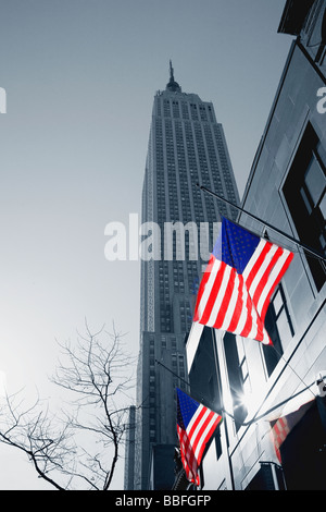 Empire State Building with stars and stripes american flags NYC USA United States of America - Stock Photo