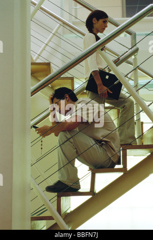 Man with hand on head sitting on stairs looking at cell phone, woman walking past - Stock Photo