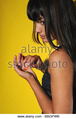 Young woman taking pills, studio shot - Stock Photo