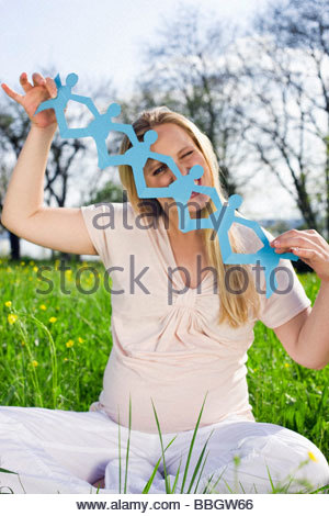 Pregnant woman holding paper dolls - Stock Photo