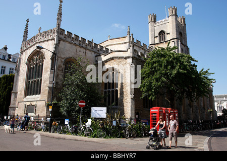 a couple strolling with a pram outside great st marys church market square cambridge uk - Stock Photo