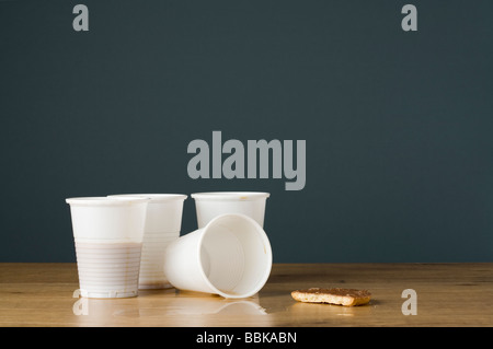 Plastic coffee cups with dregs of coffee and a half eaten biscuit - Stock Photo
