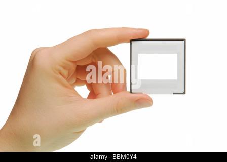 Female hand with slide frame, symbolic a presentation - Stock Photo