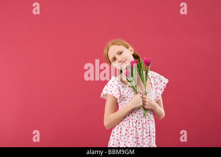 Red-haired girl with braids wearing a summer dress in front of a red backdrop with flowers - Stock Photo