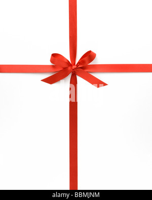 Red ribbon with bow against white background, close-up - Stock Photo