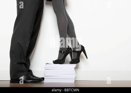 Business woman on paper pile - Stock Photo