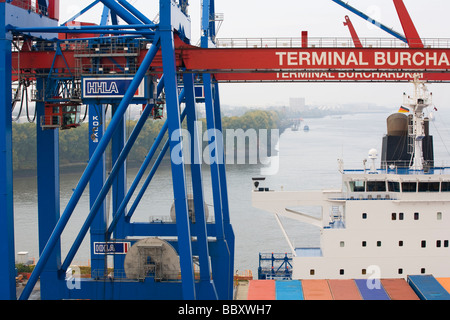Containers onboard a docked containership await to be unloaded. - Stock Photo