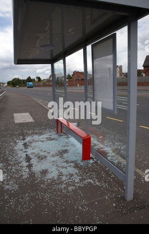 shattered glass lying on the ground from a vandalised bus shelter in northern ireland - Stock Photo