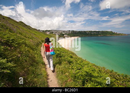 Woman in red t-shirt walking along the coastal path towards a beautiful beach - Carbis Bay in Cornwall - Stock Photo