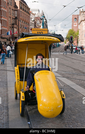 Yellow rickshaw taxi for hire in Amsterdam - Stock Photo