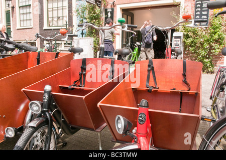 Bicycles with wooden box child seat in front, for hire in Amsterdam - Stock Photo
