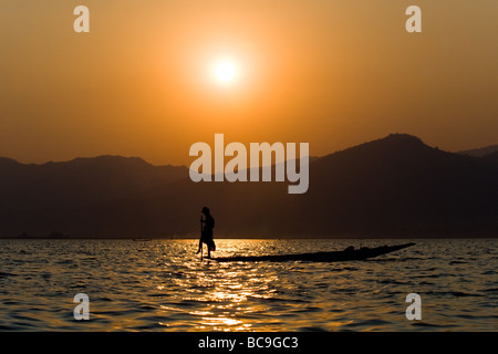 Silhouette of a rowing fisherman on Inle-Lake in Myanmar in the evening sun - Stock Photo