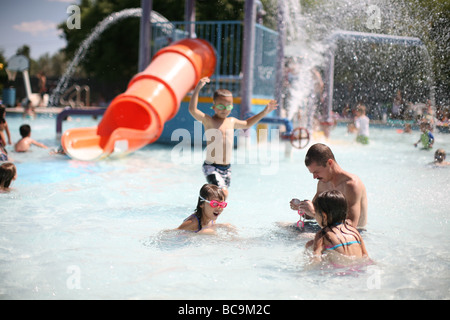 Father and children playing in swimming pool with waterslide - Stock Photo