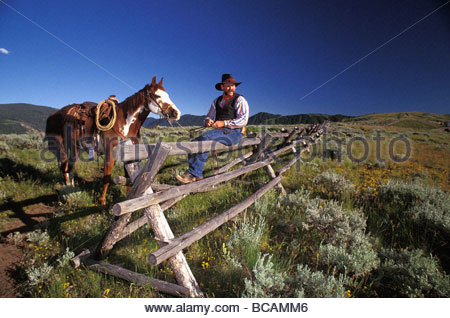 A cowboy sits with his horse on Spring Creek Ranch in Jackson, Wyoming. - Stock Photo