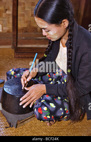 Myanmar. Burma. Bagan. A Burmese woman engraving a lacquer bowl at a lacquer workshop in Bagan. - Stock Photo