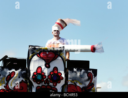 Man dressed as cigarette holding large cigarette on float in street parade - Stock Photo