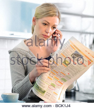 brunette woman searching a job in newspaper - Stock Photo