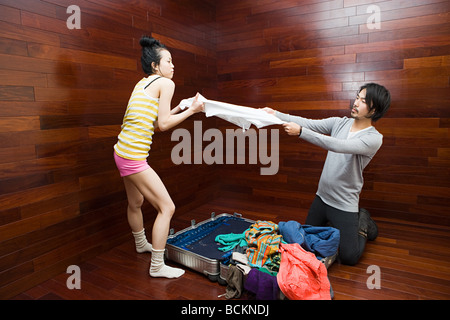 Couple fighting over clothes - Stock Photo