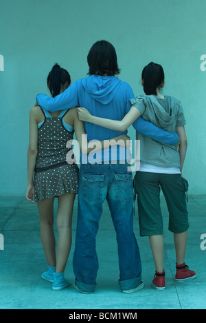 Young friends standing side by side with arms around each other, full length, rear view - Stock Photo