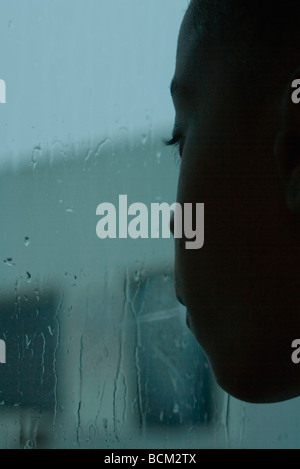 Girl looking out window on rainy day, close-up - Stock Photo