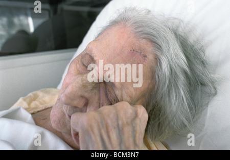 Elderly woman resting head on hand - Stock Photo