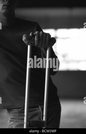 Man standing with crutch - Stock Photo