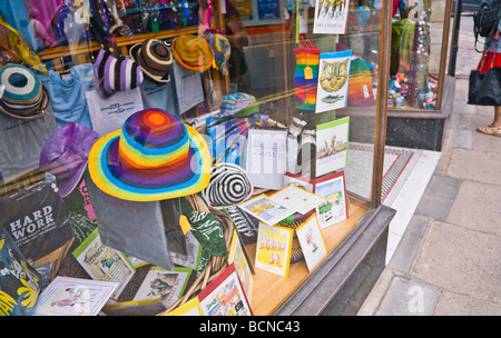 Colourful novelty hats, gifts and cards on display in a shop window. Seaside town of Swanage, Dorset. UK. - Stock Photo