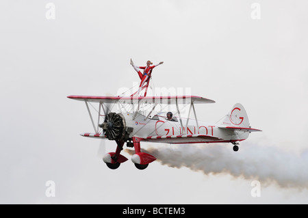 Brave lady wingwalker waving from the top wing of the Team Guinot Skincare Boeing Stearman Biplane at the 2009 Air - Stock Photo