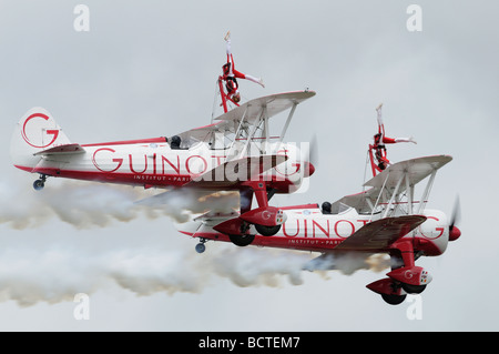 Hanging upside down on the top wing of a Boeing Stearman biplane. Team Guinot display at the 2009 Air Tattoo - Stock Photo