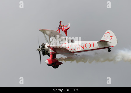 Brave young girl stands on the cockpit glass of the Team Guinot Skincare Stearman biplane as it displays at the - Stock Photo