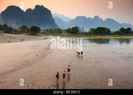 women wading the Nam Song River at Vang Vieng, Laos - Stock Photo