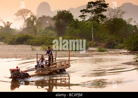 a Lao tractor wading a river at dawn nr Vang Vieng, Laos - Stock Photo