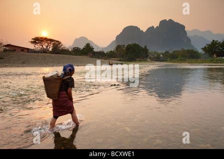 a woman fording the Nam Song River at Vang Vieng, Laos - Stock Photo