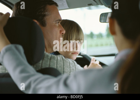 Boy sitting in father's lap in car, looking over shoulder at sister in back seat - Stock Photo