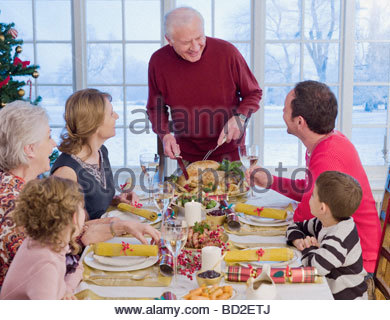 Man carving Christmas turkey at table - Stock Photo