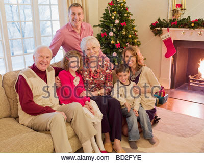 Multi-generation family near Christmas tree in living room - Stock Photo