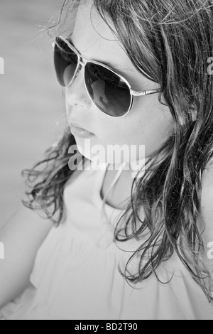 Black and White Shot of a Young Girl in Sunglasses by the Pool - Stock Photo